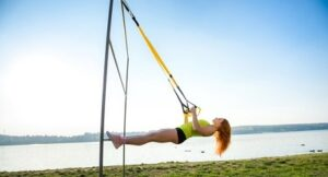 Young Woman Exercising With Suspension Trainer Sling Park Near Lake 359031 7085 300x162